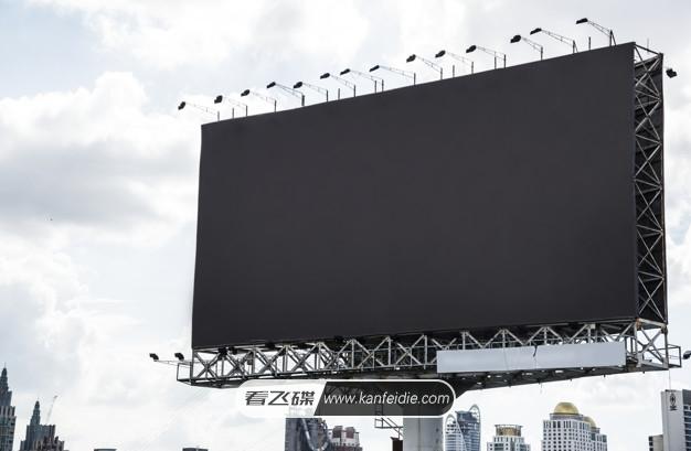 一个大型户外广告牌的PS样机模板,在广告设计中比较常用的,该场景的背景是城市的高楼,高炮是金属架组成的,然后有一块黑色的长方形横版显示屏,当然您可以在PSD分层文件中替换成您自己的广告图像。